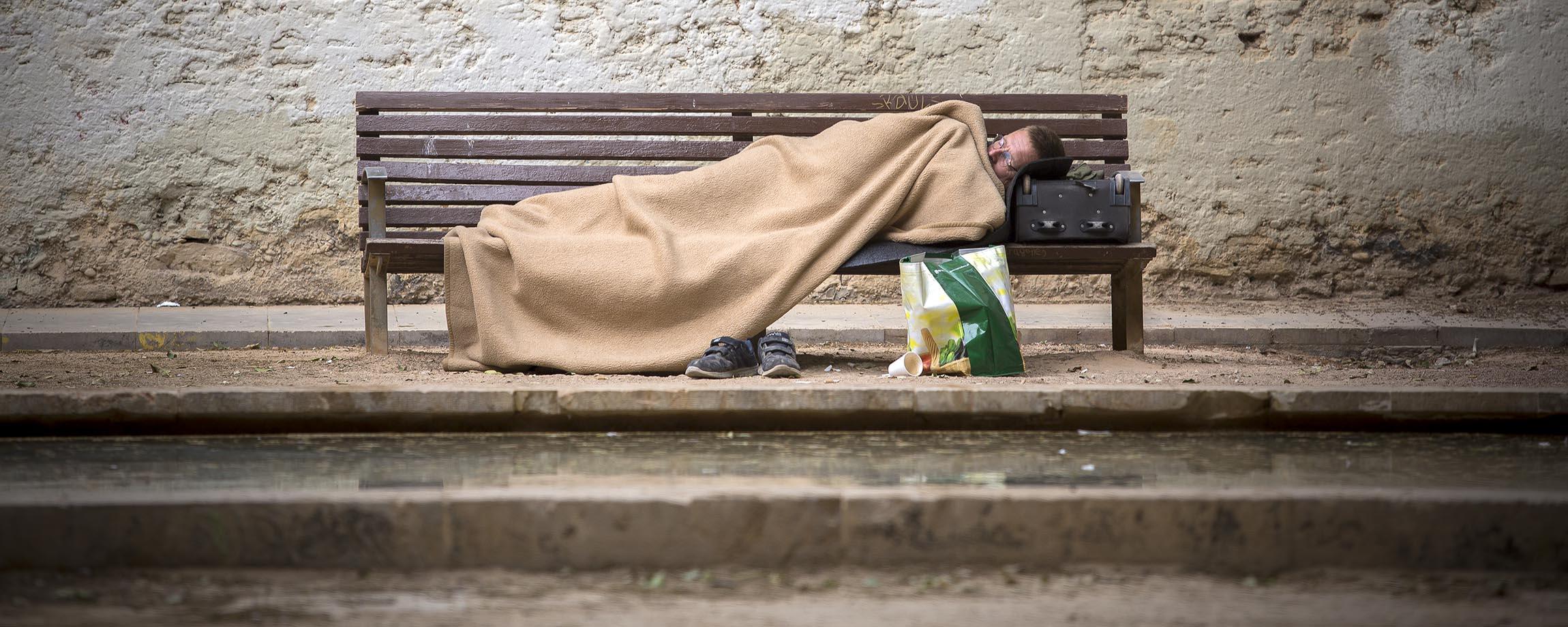 Una persona sin hogar descansa en un banco de madera | Fotografía: Marga Ferrer